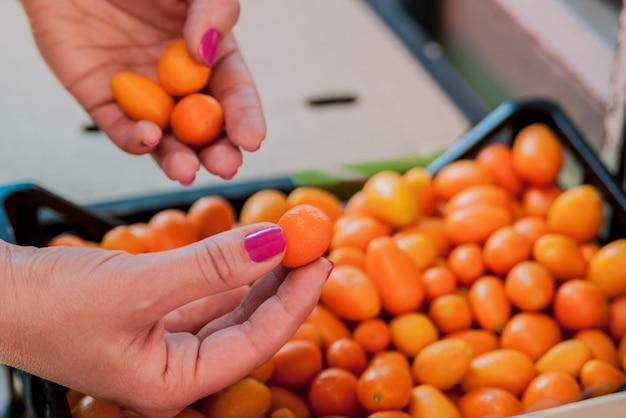 Femme tenant un tas de kumquat. femme achetant des fruits et légumes au marché alimentaire local. marché avec une variété de fruits organiques.