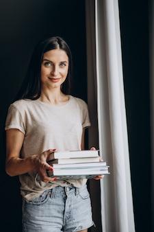 Femme Tenant Un Tas De Livres Photo gratuit