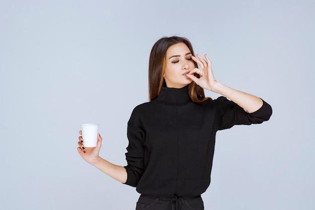 Femme tenant une tasse de café et appréciant le goût.