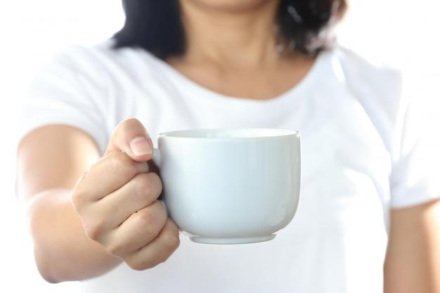 Femme tenant une tasse de café blanche.