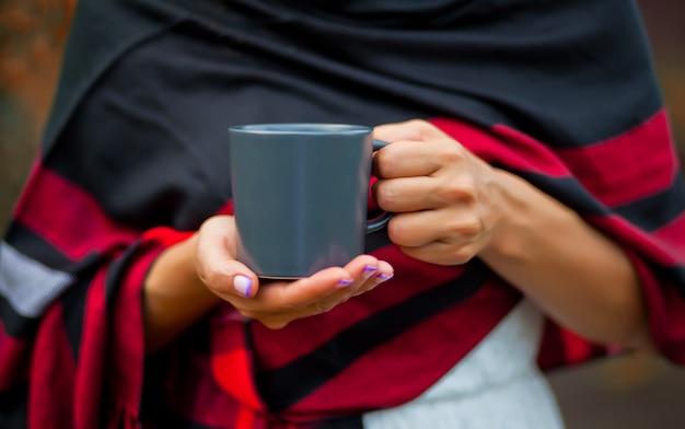 Femme tenant une tasse de café chaud dans une main