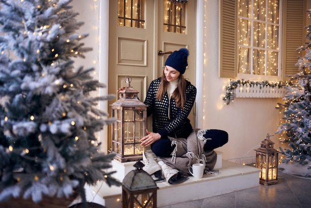 Femme tenant une tasse de café chaud en hiver près d'une fenêtre à la maison avec l'extérieur en arrière-plan.