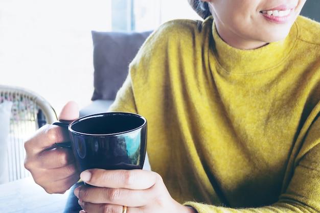 Femme tenant une tasse de café chaud à la recherche de fenêtre le matin.