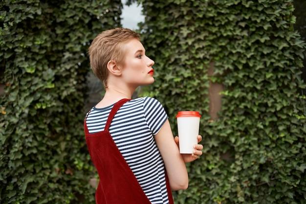 Femme tenant une tasse de café dans ses mains dans la rue près des buissons vacances d'été