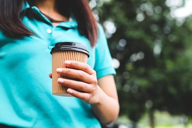 Une femme tenant une tasse de café en papier.