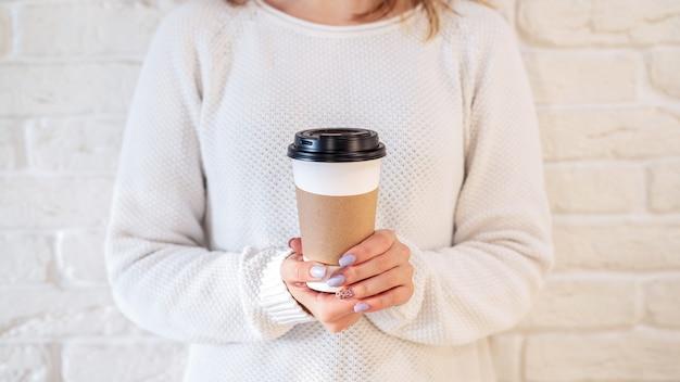Femme tenant une tasse à café recyclable. idée de recyclage