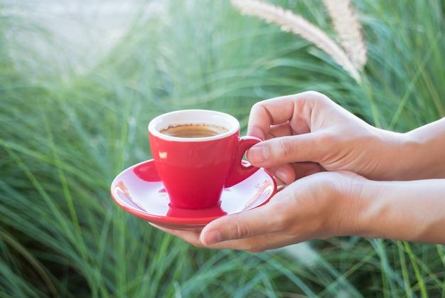 Femme tenant une tasse de café rouge (couleur de style vintage)