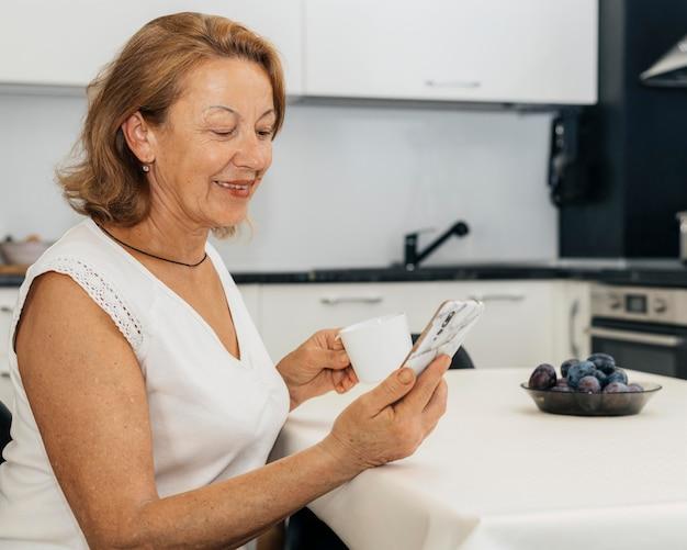 Femme tenant une tasse de café et son téléphone