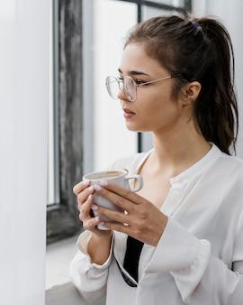 Femme tenant une tasse de café tout en travaillant à domicile
