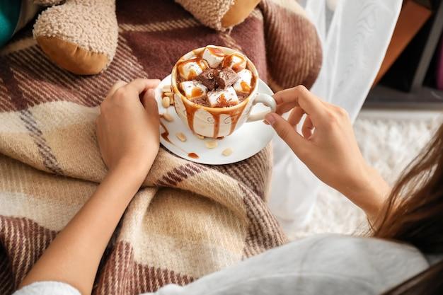 Femme tenant une tasse de chocolat chaud avec des guimauves
