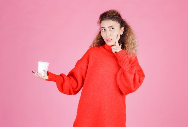Femme tenant une tasse d'eau en plastique et pensant.