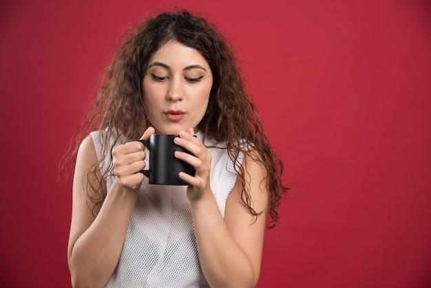 Femme tenant une tasse noire chaude sur le rouge