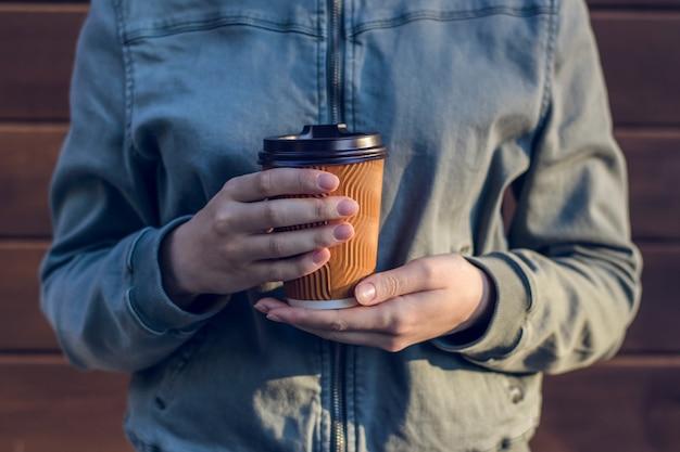 Femme tenant une tasse de papier fond en bois