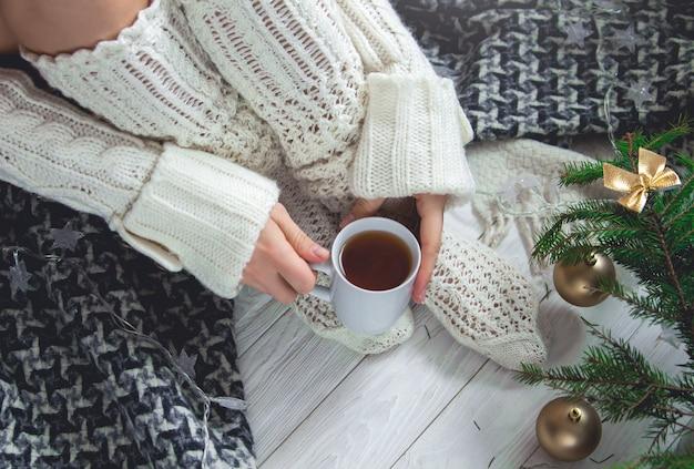 Femme tenant une tasse de thé à côté de ses jambes