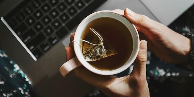 Femme tenant une tasse de thé tout en utilisant un ordinateur portable