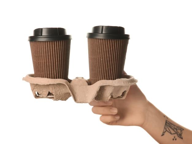 Femme tenant des tasses à café en papier sur fond blanc