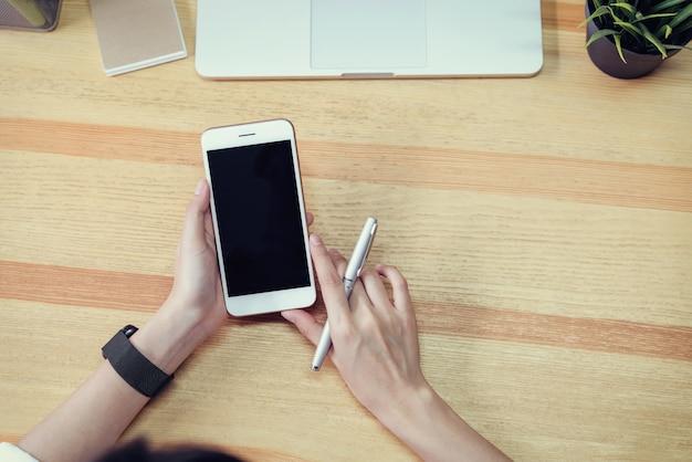 Femme tenant un téléphone à écran blanc et un ordinateur portable et mettre une montre intelligente, effet de film.