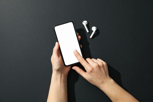 Femme tenant un téléphone avec un écran vide et des écouteurs sur fond noir, vue de dessus