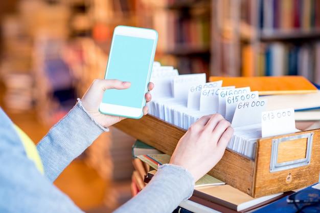 Femme tenant un téléphone intelligent avec un écran vide près du catalogue de cartes à la bibliothèque