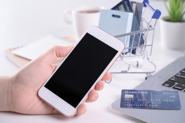 Femme tenant un téléphone mobile intelligent pour les achats de paiement électronique