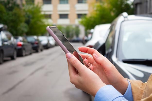 Femme tenant un téléphone portable et un taxi de réservation