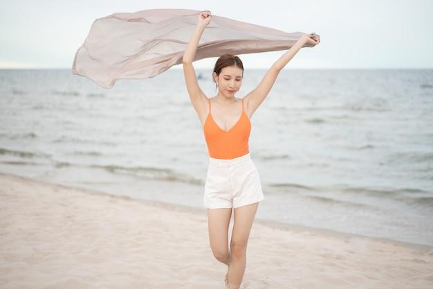 Femme tenant le tissu au vent dans des vacances de vacances à la plage. voyagez et en bonne santé.