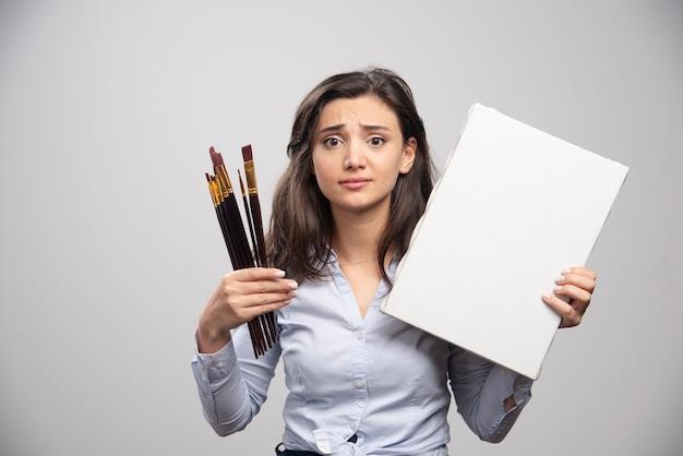 Femme tenant une toile vide et des pinceaux sur un mur gris.