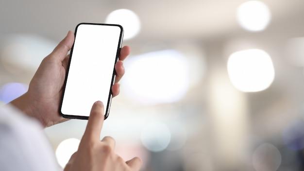 Femme tenant et touchant un smartphone à écran blanc