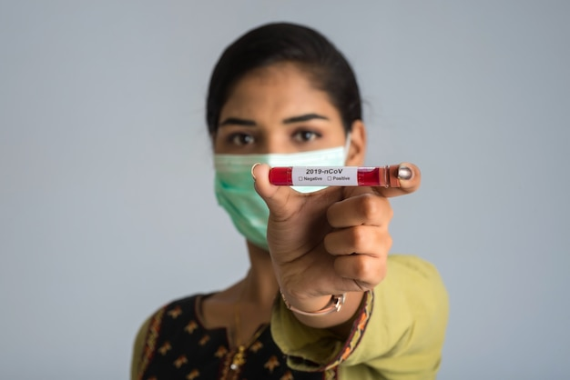 Femme tenant un tube à essai avec un échantillon de sang pour le coronavirus ou l'analyse 2019-ncov.