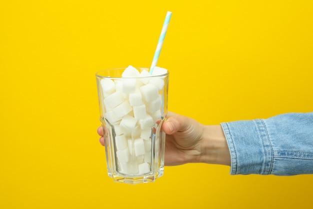 Femme tenant un verre de cubes de sucre sur une surface jaune