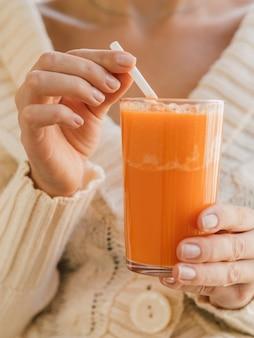 Femme tenant un verre avec du jus de carotte biologique