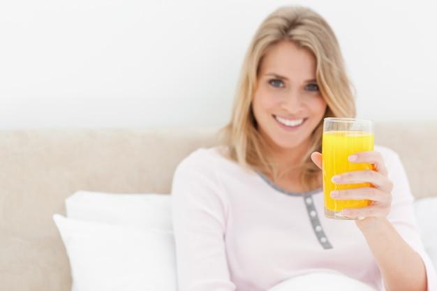 Femme tenant un verre de jus d'orange en souriant et en regardant vers l'avant