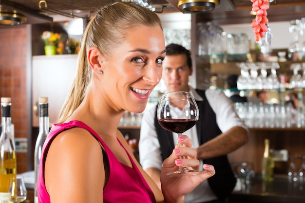 Femme tenant un verre de vin à la main au bar