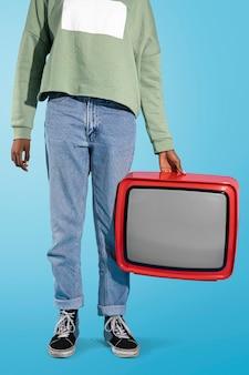 Femme tenant une vieille télévision rouge
