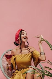 Femme tendance émotionnelle dans un bandeau lumineux, des boucles d'oreilles en argent et une robe jaune fraîche saluant et tenant un verre avec un cocktail