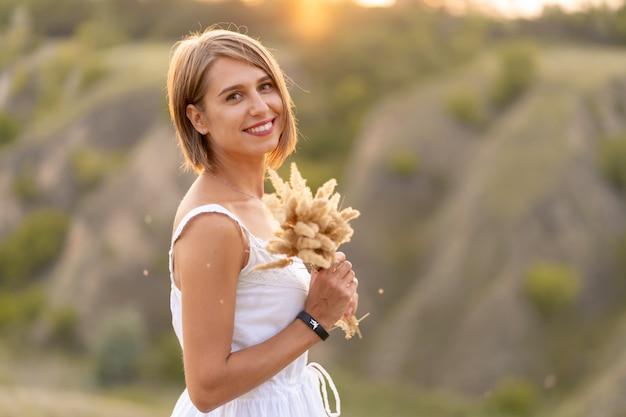 Femme tendre dans une robe d'été blanche marche au coucher du soleil dans un champ avec un bouquet d'épillets.