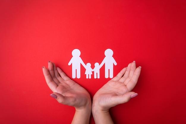 Femme tendre les mains avec un symbole de la famille découpée dans du papier blanc. protéger les droits des personnes et des minorités sexuelles