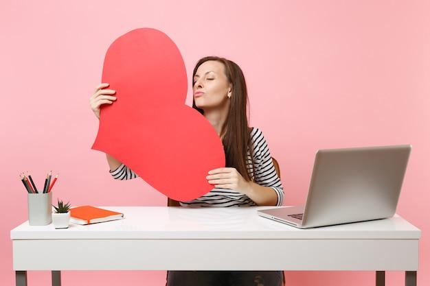 Une femme tendre soufflant des lèvres envoyant un baiser d'air tenant un coeur blanc vide rouge s'asseoir et travailler au bureau blanc avec un ordinateur portable isolé sur fond rose pastel. concept de carrière d'entreprise de réalisation. espace de copie.