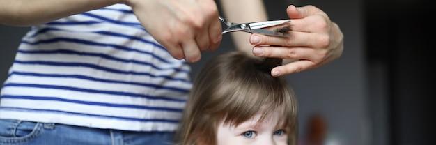 Femme tenir des ciseaux et mèche de cheveux pour enfant