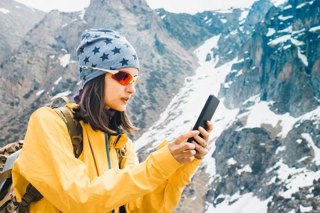 Femme tenir dans les mains un voyage de planification de téléphone portable dans la montagne de neige rock
