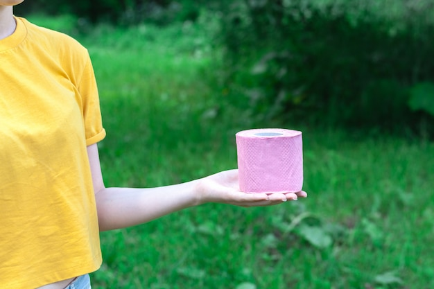 Femme tenir le papier hygiénique sur la nature. concept de diarrhée en saison estivale