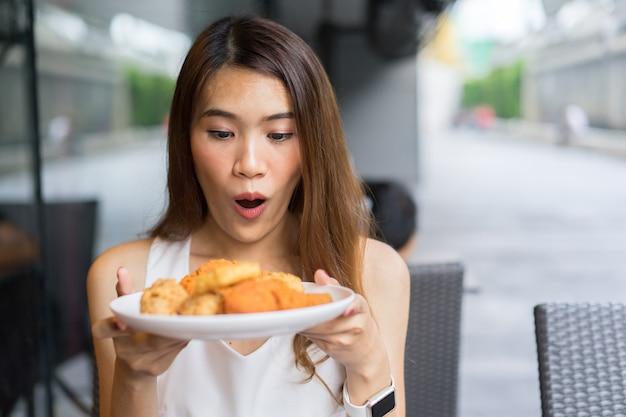 Femme tenir plat de repas de poulet frit pour manger au bar du restaurant