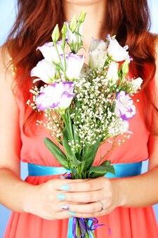Femme, tenue, bouquet, sur, fond bleu, gros plan
