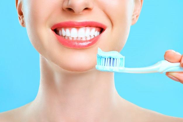 Femme, tenue, brosse dents, main, sourire