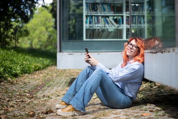 Femme en tenue décontractée regardant la caméra assise sur le sol à l'extérieur