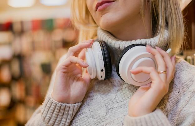 Femme, tenue, écouteurs, autour de, cou, librairie