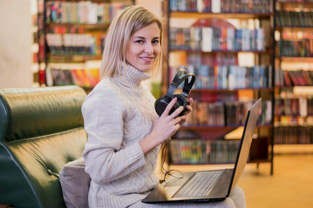 Femme, tenue, écouteurs, regarder, loin, ordinateur portable