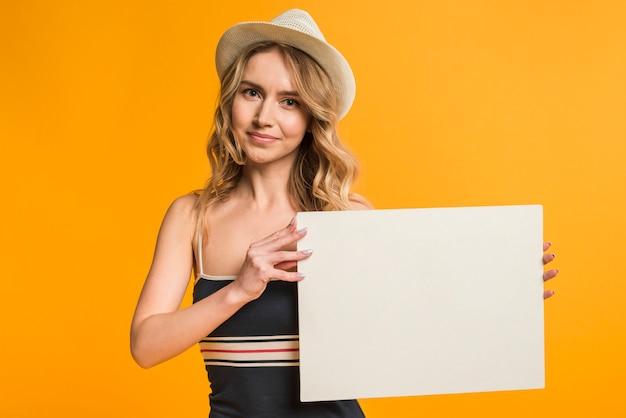 Femme en tenue d'été tenant un papier vide