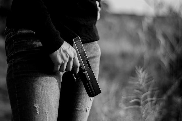 Femme, tenue, fusil, main - concept de violence et de criminalité.