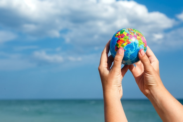 Femme, tenue, globe terre, fond, mer